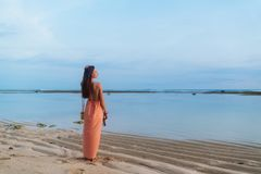 Går den slanka flickan för baksikten med långt hår i sundress med påsen på lång rem på den sandiga tropiska stranden royaltyfri foto