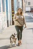 Går den stilfulla Millennial kvinnlign för den unga höften hennes husdjur Bull terrier, medan rymma en kopp av Cofffee i en gränd royaltyfri foto