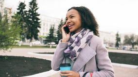 Går den talande smartphonen för den attraktiva flickan för det blandade loppet och drickakaffe i stadsgata med påsar gå kvinnabar fotografering för bildbyråer