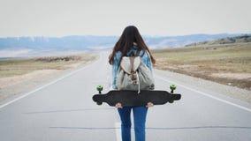 Går den tonårs- hipsteren för unga flickan på huvudvägen med longboard Med en lägerryggsäck och ett ärmlös tröjaomslag Mot arkivfilmer
