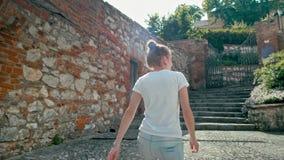 Går den turist- flickan för den tillbaka sikten med ryggsäcken i den Mikulov slotten, Tjeckien arkivfilmer