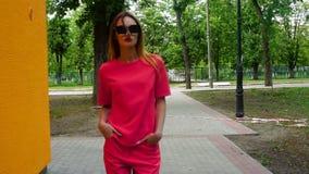 Går den unga blonda damen för glamour i röd dräkt och solglasögon ner gatan stock video
