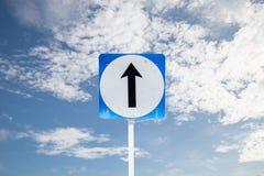 Går det raka riktningstrafiktecknet på backg för blå himmel och moln Royaltyfri Foto