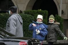 """Går skyddande maskeringar för sjuka barnkläder mot influensavirus på gatan i Sofia, Bulgarien†""""november 01, 2009 Royaltyfria Foton"""