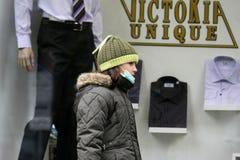 """Går skyddande maskeringar för sjuka barnkläder mot influensavirus på gatan i Sofia, Bulgarien†""""november 01, 2009 Arkivfoton"""