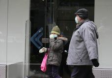 """Går skyddande maskeringar för sjuka barnkläder mot influensavirus på gatan i Sofia, Bulgarien†""""november 01, 2009 Arkivfoto"""
