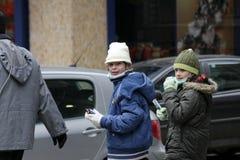 """Går skyddande maskeringar för sjuka barnkläder mot influensavirus på gatan i Sofia, Bulgarien†""""november 01, 2009 Arkivbild"""