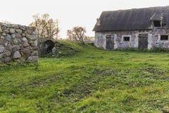 Gårdsplanen är en jordbruks- övergiven lantgård De gamla kollapsade ladugårdarna arkivfoton
