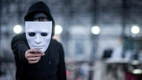 Gåtahoodieman med den svarta maskeringen som rymmer den vita maskeringen i hans hand Anonymt socialt begrepp för maskera eller fö arkivbild