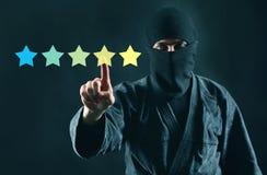 Gåtashoppare eller att granska online-begrepp Värdering direktanslutet granskning och ninja för 5 stjärnor i maskering på en mörk royaltyfria bilder