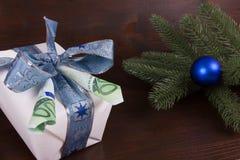 Gåva av pengar på en gåva för vit jul på mörk träbakgrund Royaltyfri Fotografi