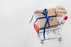 Gåva eller dag för fäder för för gåvaask och anmärkningar lycklig i shoppingvagn på ljus bakgrund arkivbilder