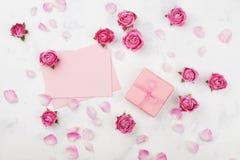 Gåva eller gåvaask, kuvert, pappersmellanrum, kronblad och rosa färgrosblomma på den vita bästa sikten för tabell i lekmanna- sti arkivbild