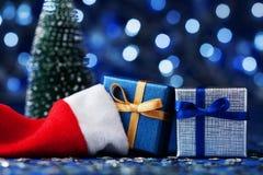 Gåva för granträd, santa hatt- och julgåvaask eller på blå bokehbakgrund Magiskt feriehälsningkort Arkivbild