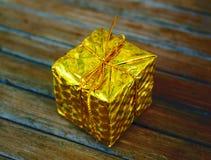 Gåva för gul guld på wood bakgrund Julgåvaask i lövverk som slår in med den guld- trådpilbågen Royaltyfria Foton