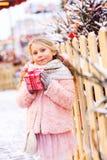 gåva för jul för lycklig barnflicka som hållande är utomhus- på gå i snöig vinterstad royaltyfri foto