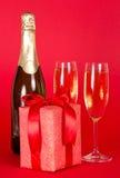 Gåva, flaska av champagne och exponeringsglas royaltyfria bilder