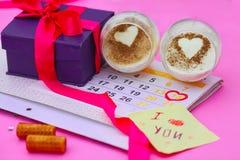 Gåva i en ask, en efterrätt och en kalender med datumet på Februari 14 Fotografering för Bildbyråer