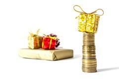 Gåva i en guld- ask med en pilbåge på en hög av kolonnnärbilden för guld- mynt som isoleras på en vit Royaltyfri Fotografi