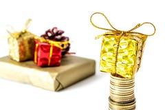 Gåva i en guld- ask med en pilbåge på en hög av kolonnnärbilden för guld- mynt som isoleras på en vit Arkivfoto