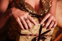 Gåva i guldpapper i whomanhanden arkivfoto