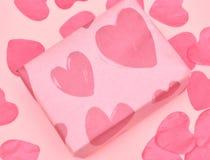 Gåva i Kraft papper med röda hjärtor på rosa bakgrund med hjärtor Begreppet av dagen för valentin` s close upp arkivfoto