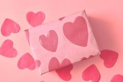 Gåva i Kraft papper med röda hjärtor på rosa bakgrund med hjärtor Begreppet av dagen för valentin` s close upp arkivbilder