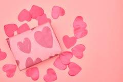 Gåva i Kraft papper med röda hjärtor på rosa bakgrund med hjärtor Begreppet av dagen för valentin` s ovanför sikt kopiera avstånd arkivfoton