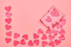 Gåva i Kraft papper med röda hjärtor på rosa bakgrund med hjärtor Begreppet av dagen för valentin` s ovanför sikt kopiera avstånd arkivbild