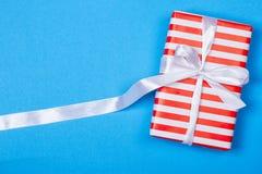 Gåva i rött och vitt emballage med bandet royaltyfri foto
