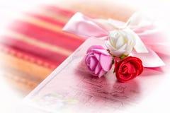 Gåva i rosa färgask med färgrika rosor royaltyfria bilder
