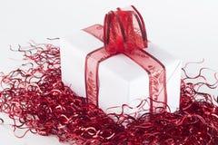 Gåva i vitbok med det röda bandet som isoleras på den vita backgroen Arkivbild