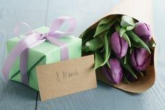 Gåva med purpurfärgade tulpan i hantverkpapper på blå wood bakgrund med 8 kortet för marsch Royaltyfria Bilder