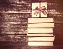 Gåva och böcker på trätabellen Royaltyfri Foto