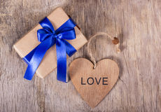 Gåva på dag för valentin` s Gåvaask med en blå pilbåge och en trähjärta kopiera avstånd valentin för dag s Royaltyfri Foto