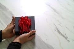 gåva som ger sig, manhand som rymmer en gåvaask i en gest av att ge nolla Royaltyfri Fotografi
