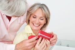 gåva som mottar den le kvinnan för pensionär Arkivbild