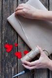 Gåva som slås in i ett kraft papper med röda hjärtor arkivbild