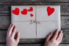 Gåva som slås in i ett kraft papper med röda hjärtor arkivfoton
