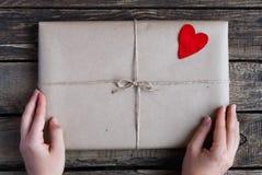 Gåva som slås in i ett kraft papper med röda hjärtor royaltyfria bilder