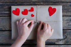 Gåva som slås in i ett kraft papper med röda hjärtor arkivfoto