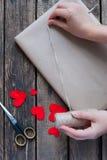 Gåva som slås in i ett kraft papper med röda hjärtor royaltyfria foton