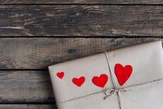 Gåva som slås in i ett kraft papper med röda hjärtor arkivbilder