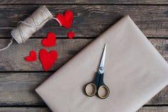 Gåva som slås in i ett kraft papper med röda hjärtor royaltyfri foto