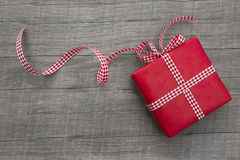 Gåva som slås in i rött papper på en träbakgrund, rutigt band Arkivfoton