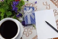 Gåva, varmt kaffe med blommor och ett ställe som ska gratuleras Arkivfoto
