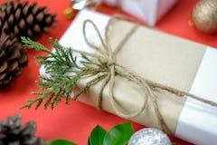 Gåvaask för vit jul på röd bakgrund som dekoreras med gräsplan arkivfoton