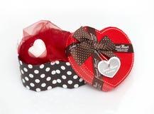 Gåvaask i formen av en hjärta med ett rött lock och en brun pilbåge Arkivbilder