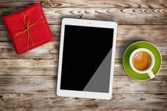 Gåvaask, kopp kaffe och digital minnestavla på träbakgrund Royaltyfri Foto