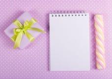 Gåvaask med den gröna pilbågen, öppen anteckningsbok med en tom sida och pinnemarshmallower på en bakgrund av prickar Royaltyfri Foto